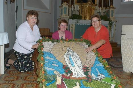 Ein von Irene Köhl, Gabi Klemens und Lydia Palm (von links) gefertigter Erntedankteppich. Darauf ist eine Maria nach dem Vorbild des französischen Wallfahrtsortes Lourdes abgebildet.